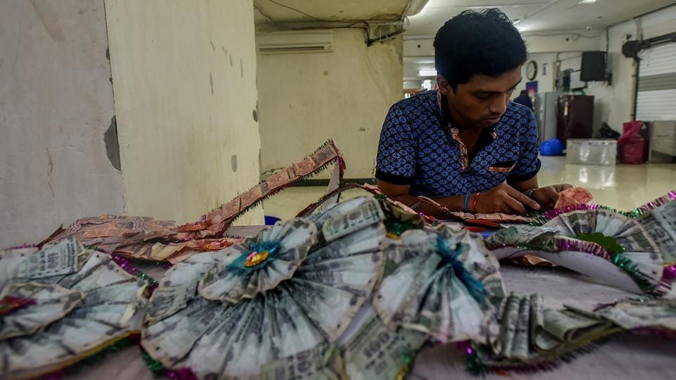 DIVIDE TO RULE: A man tries to separate the currency notes in a garland. (Kunal Patil/HT Photo)