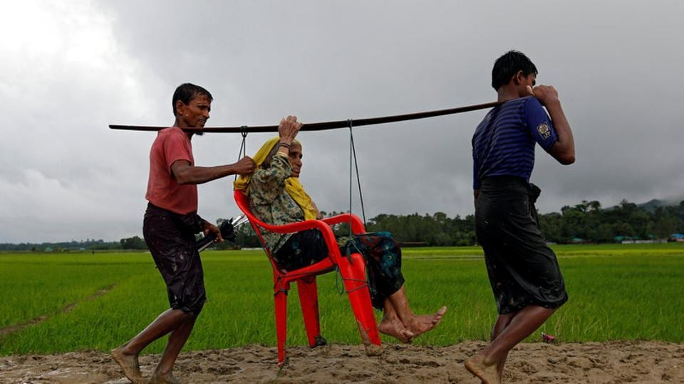 Rohingya refugee men carry an old woman as she is unable to walk after crossing the border in Teknaf, Bangladesh, on September 1, 2017.