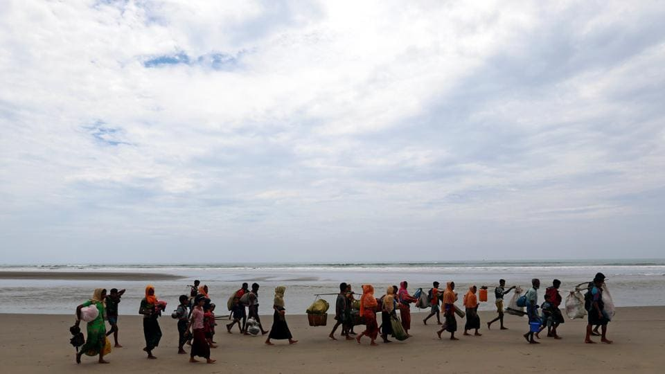 Rohingya refugees walk on the shore with their belongings after crossing the Bangladesh-Myanmar border by boat through the Bay of Bengal in Teknaf, Bangladesh, September 7, 2017.