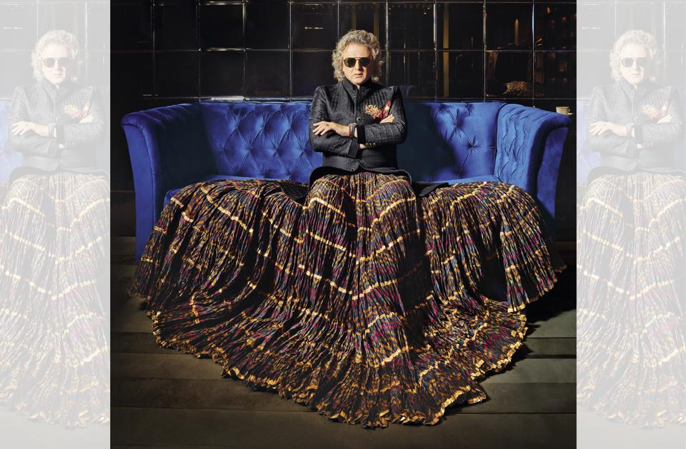 """Rohit Bal's  pet words currently are """"blessed"""" and """"balance"""", the latter also the name of his prêt label; He wears a customised emerald and gold ring from Padma Gems, sunglasses from Ray-Ban and shoes from Tod's. He wears a silk quilted short sherwani with a tiered-panel crinkled skirt with gold detailing, both from his own collection"""