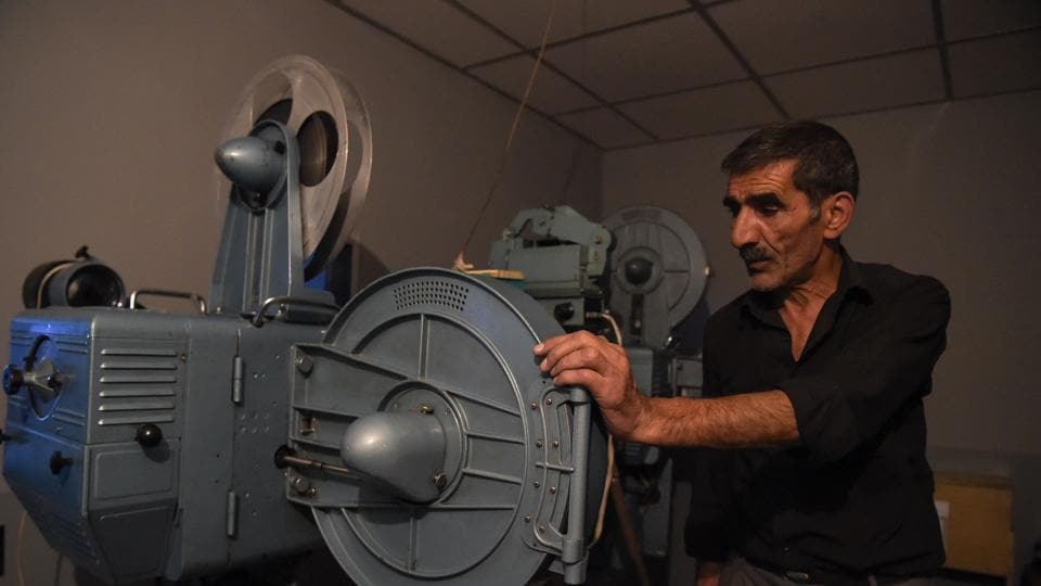 An employee preparing the screening of a film in a projection room at the state-run Afghan Film department in Kabul.