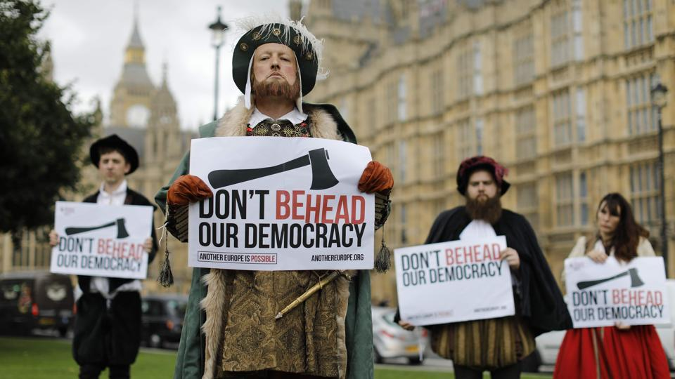 Protesters dressed in Tudor costumes, including one dressed as King Henry VIII, hold signs protesting elements of the European Union Withdrawal Bill that is being debated by lawmakers in the House of Commons in London on September 7, 2017. British lawmakers have begun debating the landmark bill to end Britain's membership of the European Union, with Prime Minister Theresa May gearing up for a major battle.