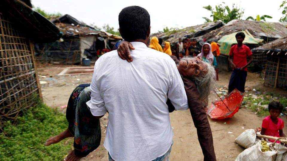 A man carries a Rohingya refugee woman from the shore after she crossed the Bangladesh-Myanmar border by boat through the Bay of Bengal in Teknaf, Bangladesh on September 7.