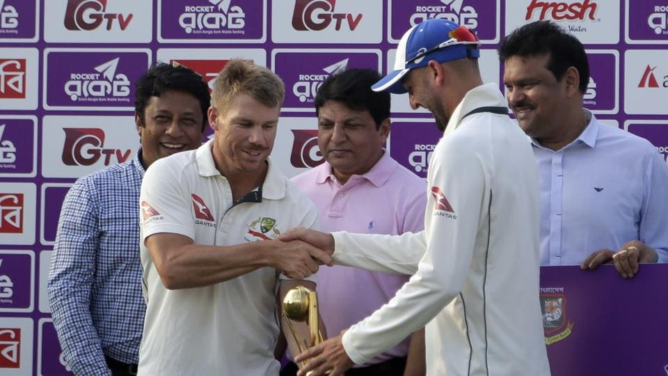 Australia's David Warner and Nathan Lyon hold the men of the series trophy jointly during a presentation ceremony after the second Test match vs Bangladesh.