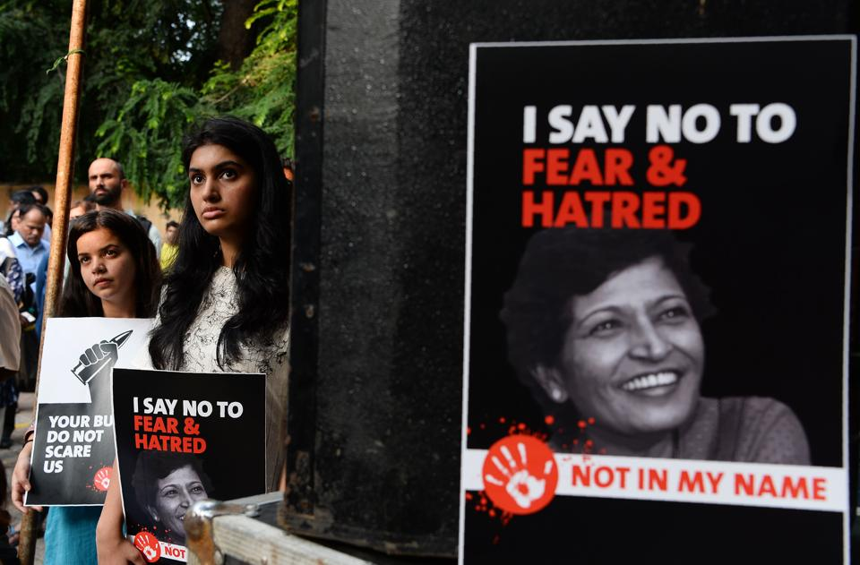 Demonstrators hold placards with the picture of Gauri Lankesh during a protest in New Delhi on Thursday.