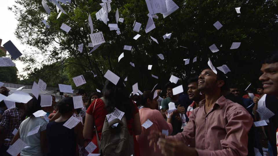 Supporters shout slogans and throw pamphlets during JNU student union election in New Delhi on Friday.