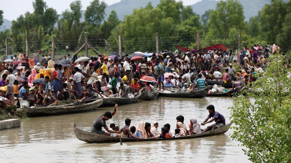A boat carrying Rohingya refugees is seen leaving Myanmar through Naf river while thousands other wait in Maungdaw on Thursday.