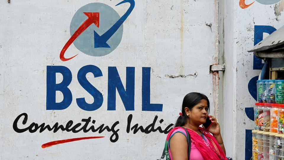A woman speaks on her mobile phone in front of the logo of Bharat Sanchar Nigam Ltd (BSNL) painted on a wall outside its office in Kolkata. BSNL has 1,30, 000 BTS and after the expansion, the total number would be 1,70,000.