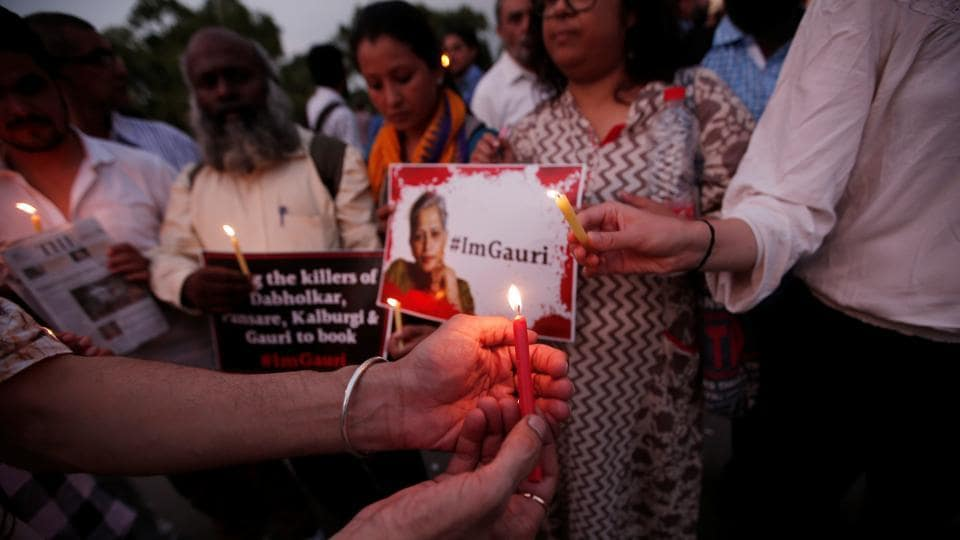People hold placards and candles during a vigil for Gauri Lankesh, a senior Indian journalist who according to police was shot dead outside her home on Tuesday by unidentified assailants in Bengaluru.