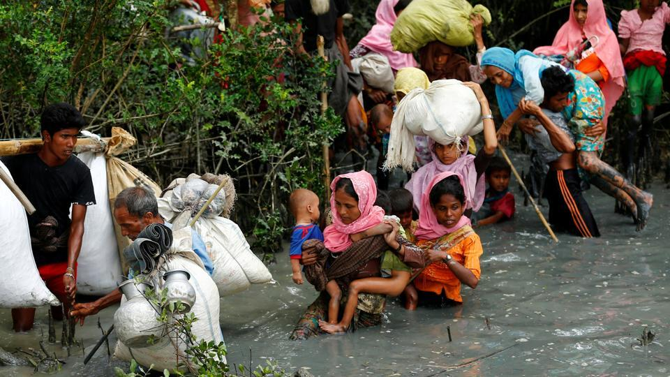 Rohingya refugees walk through water after crossing the border by boat through the Naf River in Teknaf, Bangladesh