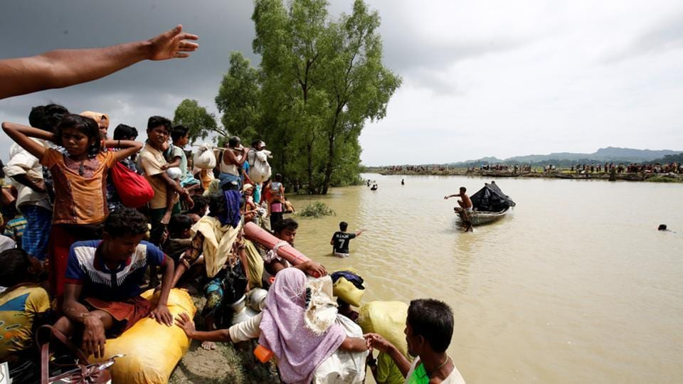 Rohingya refugees wait for a boat to cross a canal after trekking across the border through Naf river in Teknaf, Bangladesh, on September 7, 2017.