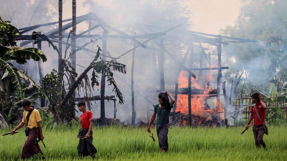 n this photograph taken on September 7, 2017, unidentified men carry knives and slingshots as they walk past a burning house in Gawdu Tharya village near Maungdaw in Rakhine state in northern Myanmar.