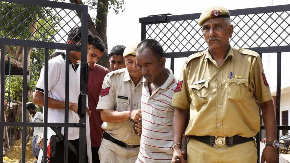 Bus conductor Ashok Kumar being escorted by police. Kumar allegedly confessed to the crime and had been remanded to three days of police custody.