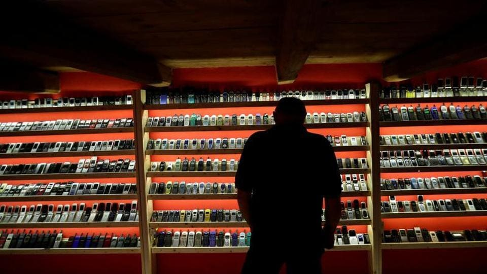 A man looks at old mobile phones inside of a private museum of phones in Dobsina.