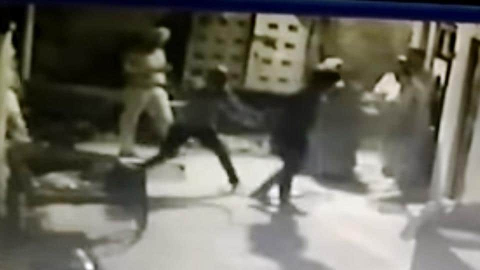 Police constable thrashing a factory owner with a stick.