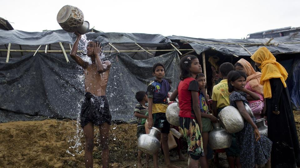 Newly arrived Rohingya wait to collect water from a tube well that was installed a few days ago, as a boy bathes beside them, at Ukhia, Bangladesh, Saturday, Sept. 9, 2017.