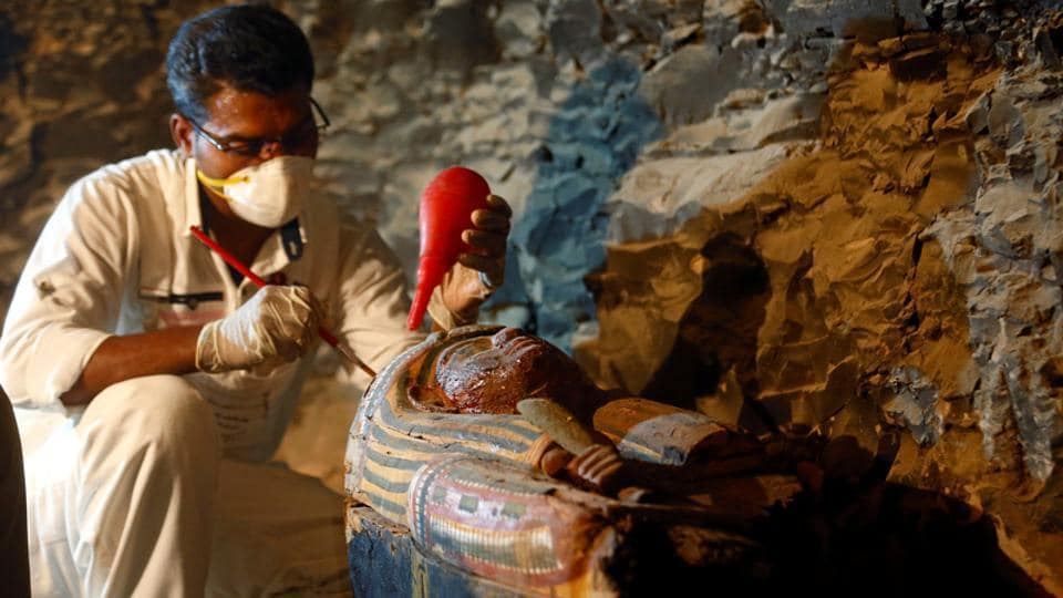 An Egyptian antiquities worker works on a coffin in the recently discovered tomb of Amenemhat, a goldsmith from the New Kingdom, at the Draa Abu-el Naga necropolis near the Nile city of Luxor, south of Cairo on September 9.