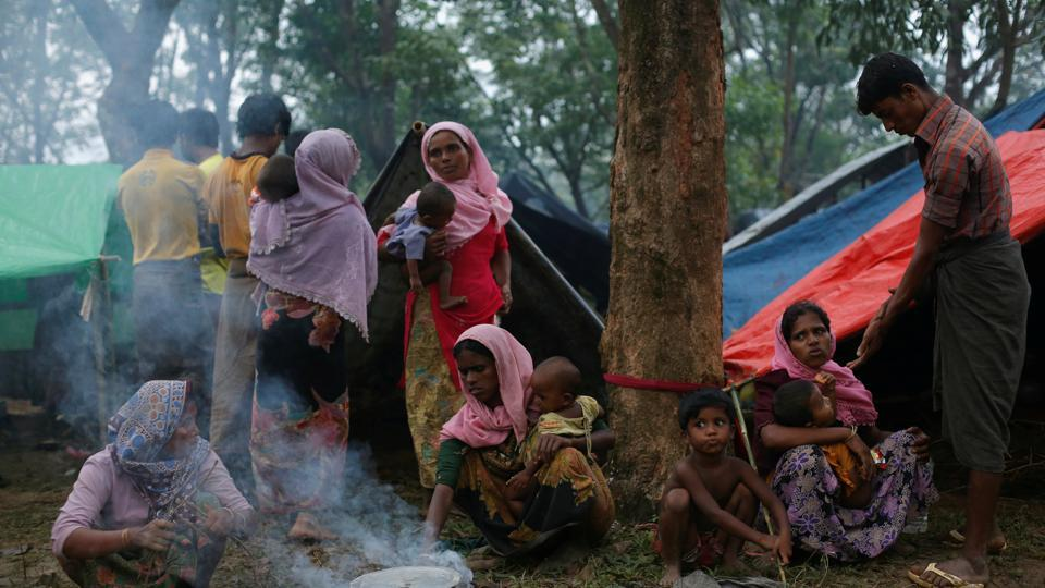 Rohingya refugees go about their day outside their temporary shelters along a road in Kutupalong, Bangladesh, September 9, 2017.