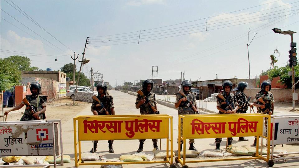 Security forces stand guard at the main entrance to the Dera Sacha Sauda headquarters, in Sirsa district of Haryana on Friday, ahead of the search operations inside the premises.