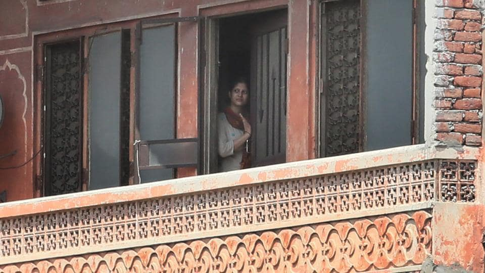 A woman looks at deserted Ramganj Chaupar after curfew was imposed following arson by mob.