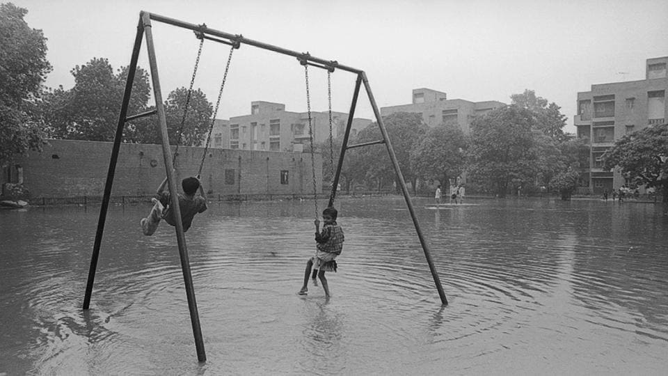 A look at Delhi's monsoon season from decades ago reveals a picture of joy among its residents, even through the daily inconveniences of wading through water in traffic.  (S Burmaula / HT Photo)