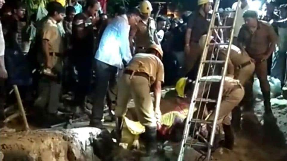Fire brigade personnel and policemen retrieving the bodies of two teenagers who drowned in a septic tank in a village in West Bengal's Murshidabad district.
