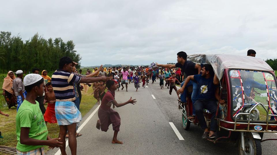 Rohingya Muslim refugee children follow a vehicle with relief supplies near the Bangladeshi town of Teknaf on Sunday.