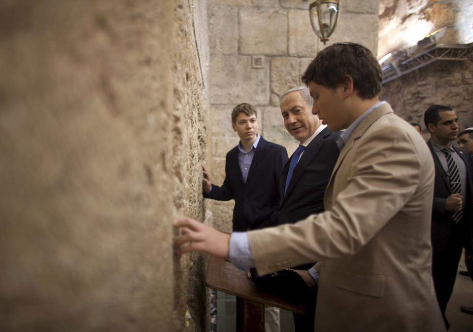 Israeli Prime Minister Benjamin Netanyahu (centre) prays with his sons Yair (background) and Avner (right) at the Western Wall — the holiest site where Jews can pray — in Jerusalem's Old City on January 22, 2013.