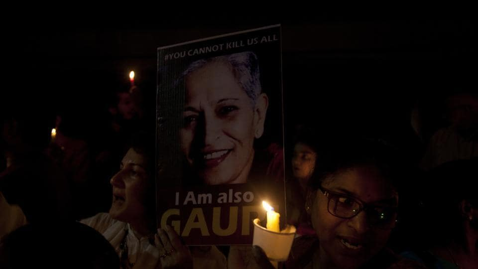 Protesters in Hyderabad hold candles and placards during a candle light vigil to protest the killing of journalist Gauri Lankesh.