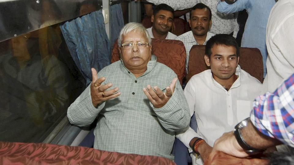 RJD chief Lalu Prasad with his son and leader of opposition Tej Pratap Yadav inside a train at Patna on Saturday.
