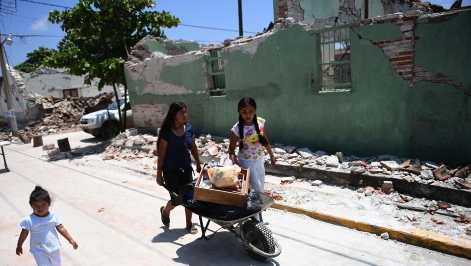 People walk by buildings knocked down by an 8.1 magnitude earthquake, in Oaxaca, Mexico, on Saturday.