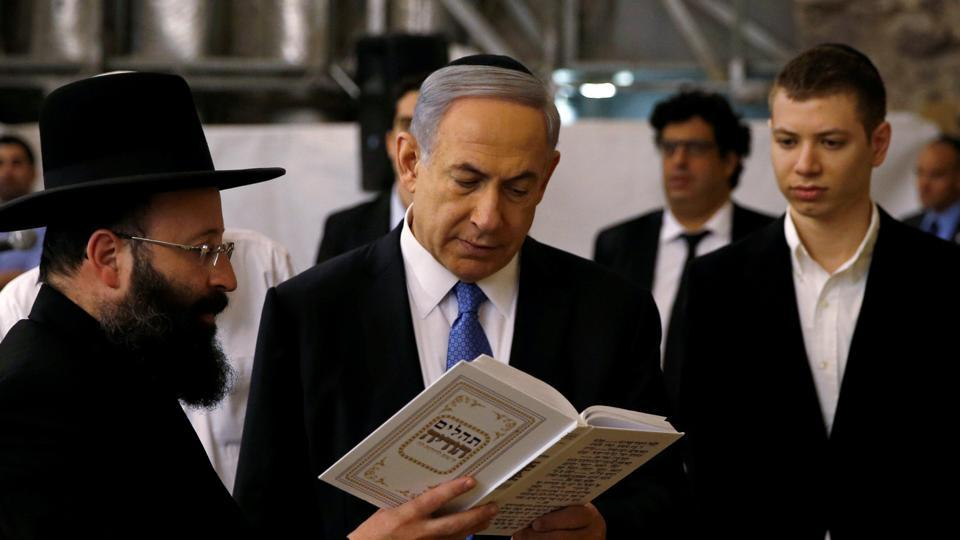 Israel's Prime Minister Benjamin Netanyahu (Centre) reads a prayer with Western Wall Rabbi Shmuel Rabinowitz as his son Yair (right) stands next to him, at the Western Wall, in Jerusalem's Old City in March.