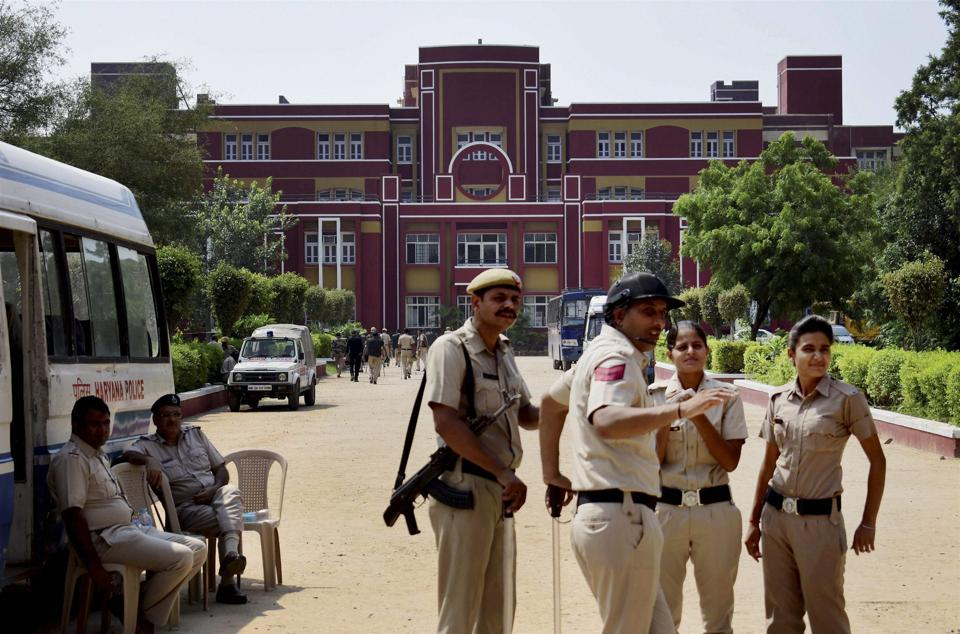 Police stand guards at Ryan International School during a protest, in Gurugram on Saturday.