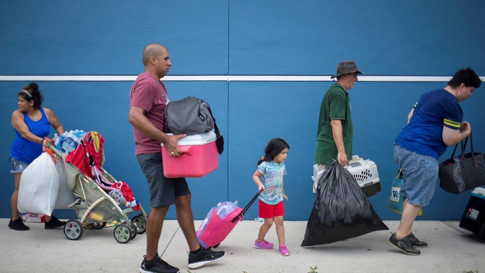 Residents carry their belongings into a shelter ahead of the downfall of Hurricane Irma in Estero, Florida.