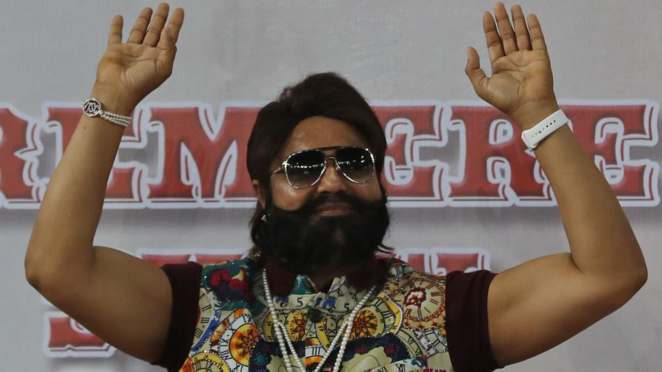 In this file photo, Gurmeet Ram Rahim Singh gestures during the premiere of a movie in New Delhi.
