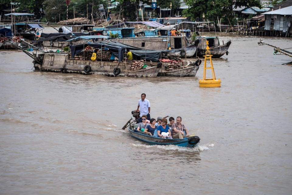 Tourists ride a boat in a canal off the Song Hau river in the floating Cai Rang market in Can Tho on July 17, 2017.