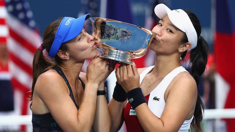 Martina Hingis and Yung-Jan Chan kiss the US Open women's doubles trophy after defeating Lucie Hradecka and Katerina Siniakova.