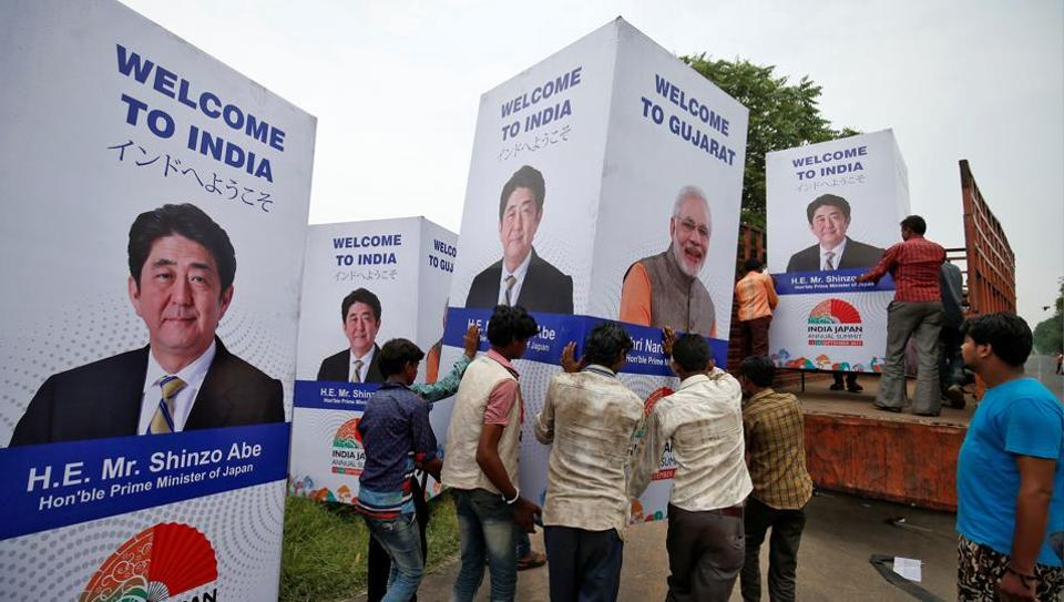 Workers carry a hoarding featuring Prime Minister Narendra Modi and his Japanese counterpart Shinzo Abe ahead of Abe's visit in Ahmedabad.