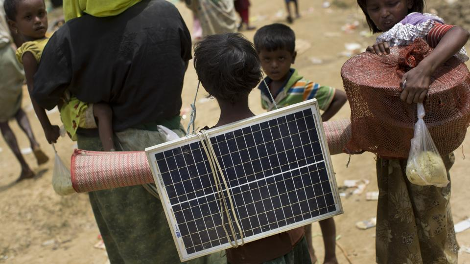 A Rohingya Muslim child carries a solar panel as she crosses over the border from Myanmar into Bangladesh in Teknaf area. Small solar panels are everywhere in the makeshift refugee camp that has sprouted up to accommodate many of the more than 270,000 people the UN says have entered Bangladesh since the violence started. The dark-blue-and-white panels are also perched on the plastic roofs of their shelters. 'We got it so that in the dark we can have some light,' said one man. (Bernat Armangue / AP)