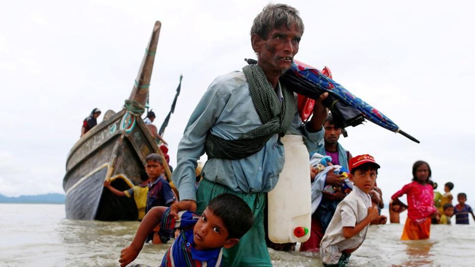 A Rohingya refugee man pulls a child as they walk to the shore after crossing the Bangladesh-Myanmar border by boat through the Bay of Bengal in Shah Porir Dwip, Bangladesh, September 10.