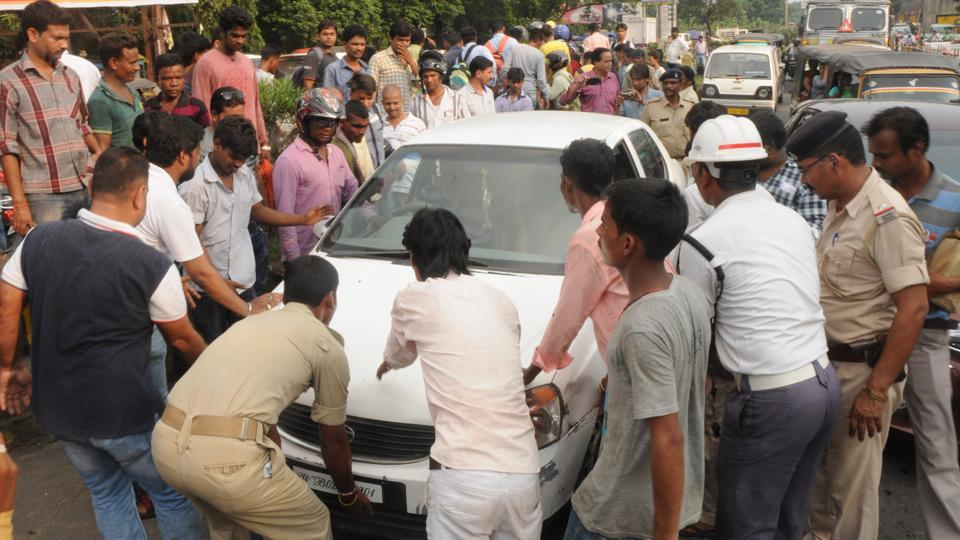 Locals trying to remove the car from the road as the driver fled leaving the vehicle abandoned on seeing police check at RD Tata Square in Jamshedpur on Monday.