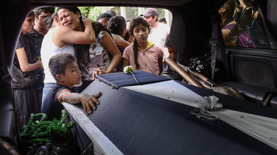 Relatives of late policeman Juan Jimenez mourn him during a funeral of victims of the 8.1-magnitude earthquake that hit Mexico's Pacific coast, in Juchitan de Zaragoza, Mexico on September 10, 2017. Sobbing Mexican families followed coffins through the streets and picked nervously at the ruins of their homes Sunday as help trickled in after the huge earthquake killed 91 people. (Victoria Razo / AFP)