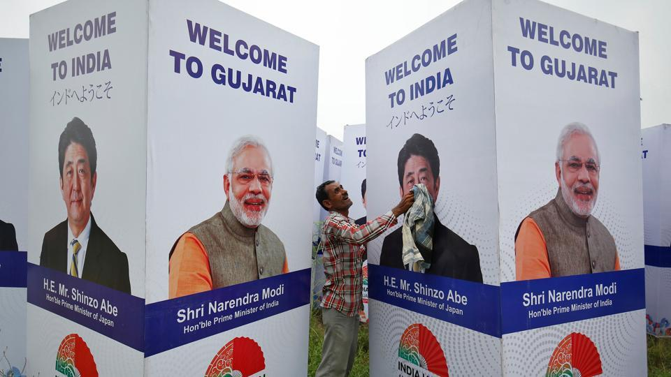A worker cleans a hoarding featuring Prime Minister Narendra Modi and his Japanese counterpart Shinzo Abe ahead of Abe's visit, in Ahmedabad on September 10.