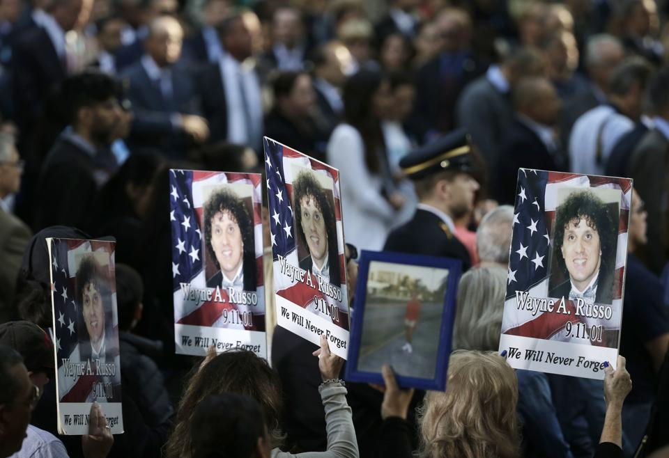 People hold up signs with the names and pictures of victims of the 9/11 terrorist attacks during a ceremony at ground zero in New York. Nearly 3,000 people died when hijacked planes slammed into the trade center, the Pentagon and a field near Shanksville, Pennsylvania, on September 11, 2001, hurling America into a new consciousness of the threat of global terrorism. (Seth Wenig / AP)