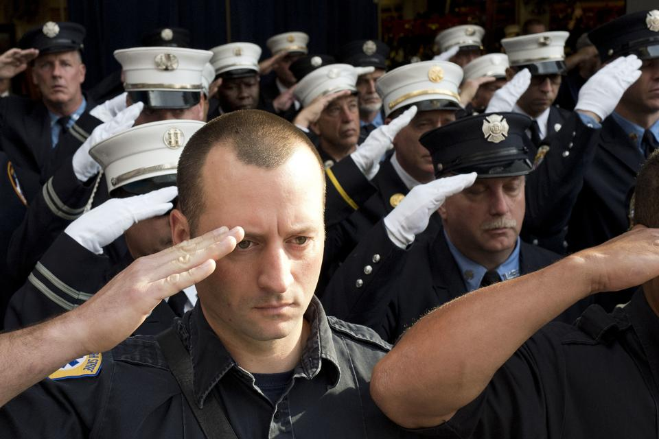 New York City firefighters with Ladder 10 Engine 10 firehouse salute during the moment of silence at the World Trade Center in New York. During the attacks of 9/11, 343 firefighters were killed.  (Mark Lennihan / AP)