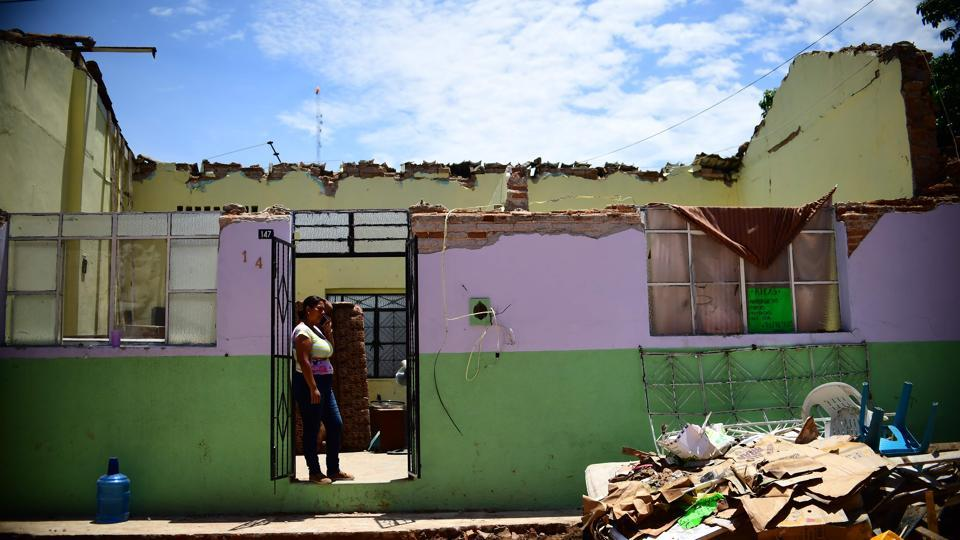 A woman stands at the door of her partially collapsed house as she prepares to evacuate it, in Tonala, Chiapas State, Mexico. Thursday's quake was bigger even than the 8.1 quake that killed 10,000 people in Mexico City in 1985 and the biggest in 100 years according to President Enrique Pena Nieto who declared three days of national mourning and pledged to rebuild shattered towns and villages. (Ronaldo Schemidt / AFP)