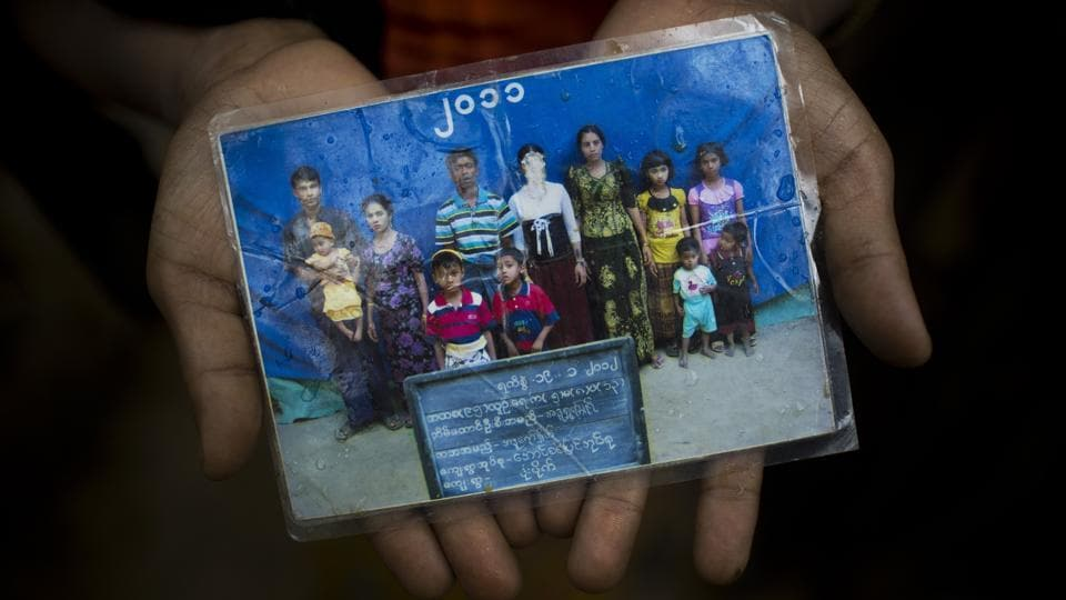 Mubarak Begum, holds a photograph of her family members, in Bangladesh. She says the government took pictures of Rohingya families annually to track numbers. Her daughter Rubina (face scratched) couldn't make it across and is still in Maungdaw. An estimated 300,000 Rohingya have fled in the fortnight since August 25, 2017. As thousands pour into Bangladesh escaping shootings, arson, violence and growing reports of landmines along the border, most carry but a handful from life back home. (Bernat Armangue / AP)