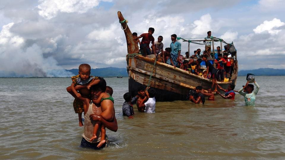 Smoke is seen on Myanmar's side of the border as Rohingya refugees get off a boat after crossing the Bangladesh-Myanmar border through the Bay of Bengal in Shah Porir Dwip on September 11, 2017.