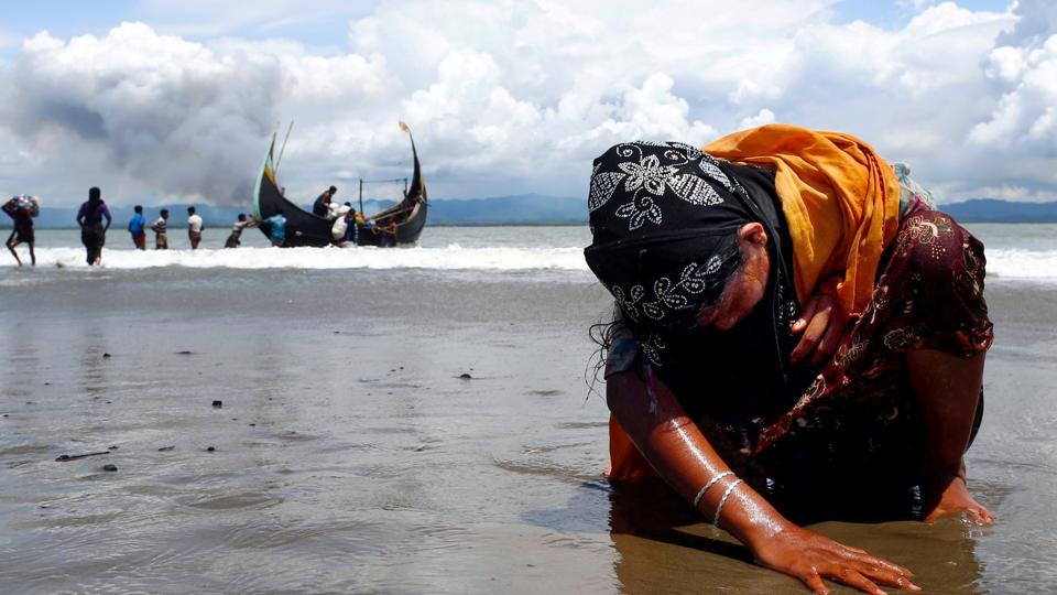 An exhausted Rohingya refugee woman touches the shore after crossing the Bangladesh-Myanmar border by boat through the Bay of Bengal, in Shah Porir Dwip, Bangladesh, on Monday.