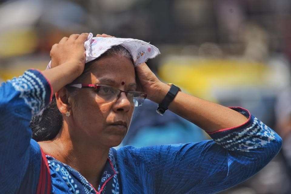A woman tries to protect her head from the heat at Dadar.